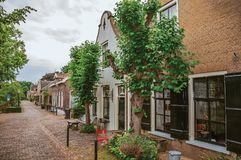 Charming and quiet street with brick rustic houses and greenery in cloudy day at Drimmelen. royalty free stock images