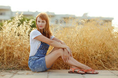 Charming red-haired girl in denim overalls sitting on a backgrou Stock Images