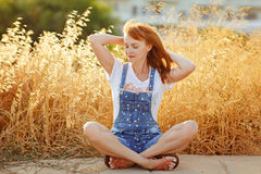 Charming red-haired girl in denim overalls sitting on a background of yellow dry grass at sunset in summer royalty free stock photography