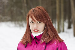 Charming red-haired girl in winter wood Royalty Free Stock Photos