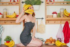 Charming red-haired slim girl sits on the table on the background of kitchen shelves with jars, around her a lot of fresh yellow b royalty free stock images