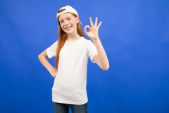 Charming Red-haired Teenager Girl In A White T-shirt Shows A Blank Print Space On A Blue Studio Background Royalty Free Stock Image