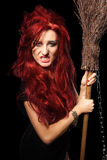 Charming red-haired witch with broom. Stock Photo