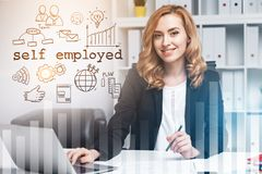 Successful beautiful self employed businesswoman. Charming red haired woman sitting in office near a self employed text and icons drawing. Graphs in the stock photo