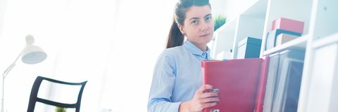 A young girl in the office takes out a folder with documents from the shelter. Charming red-haired young girl in a blue blouse is working in a bright office royalty free stock images