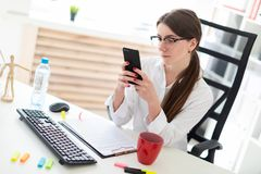 A young girl is sitting at a table in the office, looking at the phone and beside is a cup. Charming red-haired young girl in glasses and a white blouse is Stock Images