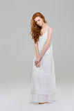 Charming redhead woman in dress. Full length portrait of a charming redhead woman in dress standing over gray background Royalty Free Stock Images