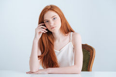 Charming redhead woman sitting at the table Stock Photo
