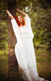 Charming redhead woman wearing white dress stands near tree Stock Photos