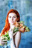 Charming romantic female woman holds Gloriosa Orange on blue background. Flower shop and floristic design master class concept on painted blue wall loft style Stock Photo
