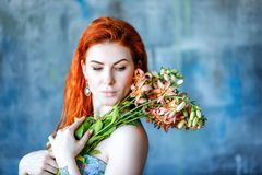 Charming romantic female woman holds Gloriosa Orange on blue background. Flower shop and floristic design master class concept on painted blue wall loft style Royalty Free Stock Photography