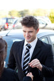Charming salesman giving a customer car keys. Outside royalty free stock photos