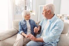 Charming senior couple holding hands while sitting on sofa Royalty Free Stock Photos