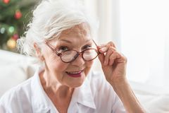 Charming senior female is posing with smile. Positive mood. Close-up portrait of elegant elderly lady who is expressing gladness. She is looking at camera with royalty free stock photography