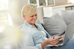 Charming senior woman shopping on internet Stock Photos