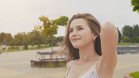 A charming sensual young girl in a summer dress is walking along the park in the center of the city. Her long hair flies. In the wind. Enjoying a summer`s day stock video