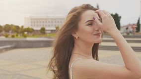A charming sensual young girl in a summer dress is walking along the park in the center of the city. Her long hair flies stock video