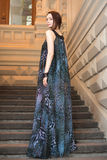 Charming sensual young woman in gauzy lengthy dress on stairs. Charming lovely woman in gorgeous dress is posing on stairs of historic building Stock Images