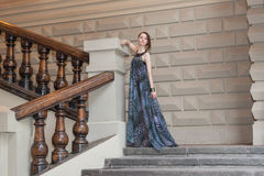 Charming sensual young woman in gauzy lengthy dress on stairs. Charming lovely woman in gorgeous dress is posing on stairs of historic building Royalty Free Stock Photo