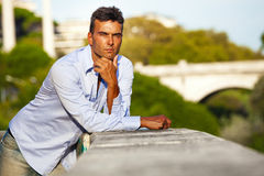 Charming serious Italian man outdoors leaning on a wall. Rome, Italy Stock Photo