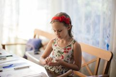 A charming seven-year-old girl enthusiastically creates paper crafts. Hobbies and interests stock photos