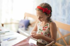 A charming seven-year-old girl enthusiastically creates paper crafts. Hobbies and interests royalty free stock image