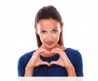 Charming and sexy female making a love sign Royalty Free Stock Image