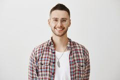 Charming shop assistant ready to offer his help. Portrait of attractive emotive young man with beard in eyewear smiling Royalty Free Stock Photography