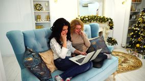 Charming sisters decided to triple movie evening on laptop sitting on sofa in bright living room with festive fireplace stock video
