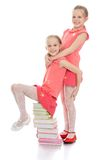 Charming sisters frolic sitting on a stack of Royalty Free Stock Photography