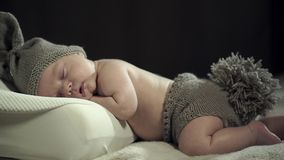 A charming sleeping baby in knitted cap with ears and shorts with a tail. The camera moves right to the left stock video footage