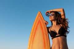 Charming slim dark-haired girl in a swimsuit and sunglasses stands near yellow surfboard on a sunny day stock photography