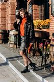 Charming slim girl dressed in skirt, orange blouse and black down jacket with fur on it walks in the street royalty free stock photo