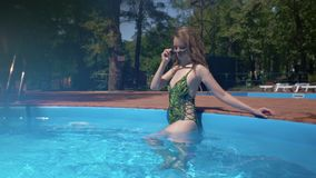 Charming slim woman is standing in shallow of pool, camera is moving to her face, she is smiling stock footage
