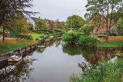 Charming small canal next to rustic houses with lush gardens and trees reflected on the water in cloudy day at Drimmelen. royalty free stock photos