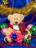 Charming small teddy bear with Christmas gift Royalty Free Stock Images
