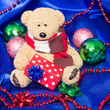 Charming small teddy bear with Christmas gift Royalty Free Stock Photography