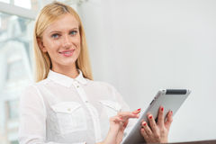 Charming smile. Business woman holding a tablet in her hands and Stock Photo