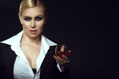 Charming smiling blond wearing white male shirt and holding a glass of brandy. Close up portrait of charming smiling blond model with pulled back hair and smoky Royalty Free Stock Images
