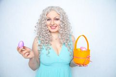 Charming smiling blonde teenager stands in a blue dress with an orange basket with painted eggs for Easter alone on white studio s. Olid background alone stock photo