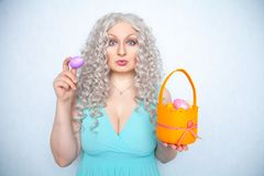 Charming smiling blonde teenager stands in a blue dress with an orange basket with painted eggs for Easter alone on white studio s. Olid background alone stock images