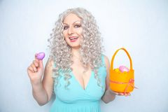 Charming smiling blonde teenager stands in a blue dress with an orange basket with painted eggs for Easter alone on white studio s. Olid background alone royalty free stock photo