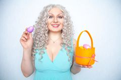 Charming smiling blonde teenager stands in a blue dress with an orange basket with painted eggs for Easter alone on white studio s. Olid background alone royalty free stock images