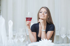Charming smiling girl drinking wine in restaurant Royalty Free Stock Photography