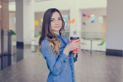 Charming smiling happy woman dressed in jeans shirt is drinking latte while doing shopping in a mall takeaway coffee shop to go wa stock image