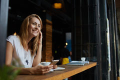 Charming smiling hipster girl received good news on cell telephone while she sitting in cozy coffee shop Stock Photography