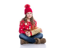 Charming smiling little girl with curly hairstyle wearing red knitted sweater and hat holding christmas gift isolated on white. Stock Images