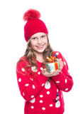 Charming smiling little girl with curly hairstyle wearing red knitted sweater and hat holding christmas gift isolated. Stock Photos