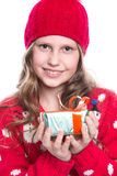 Charming smiling little girl with curly hairstyle wearing red knitted sweater and hat holding christmas gift isolated on white. Stock Image