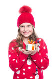 Charming smiling little girl with curly hairstyle wearing red knitted sweater and hat holding christmas gift isolated on white. Royalty Free Stock Image